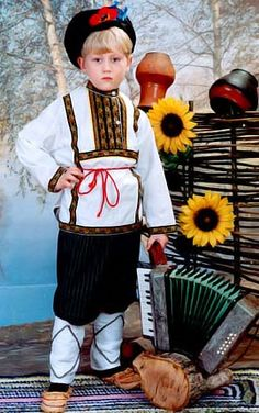 A Russian folk boy's suit is hand made, not mass produced. Embroidered ribbons decorate the shirt on the chest, sleeves, and along the shirt's bottom. A matching belt adds a final touch. The hat/cap is called a Kartuz; Valenki felt boots are traditional footwear.