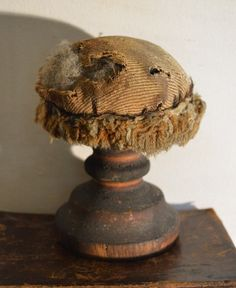 "Folky old pincushion with a wool top and some sheep's wool peeking out. 6"" tall."