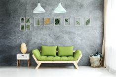 Set of framed tropical leaves and pastel lamps hanging above green wooden sofa, white cupboard and wicker basket with pillows Above Couch, White Cupboards, Monochromatic Color Scheme, Green Sofa, Wooden Sofa, White Sofas, Carpet Flooring, Tropical Leaves, Interior Styling