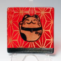 "This catch-all features our lucky cat ""Maneki Neko"" screen printed in black enamel over a Japanese geometric design, printed in gold mica, onto transparent red-orange glass, then fused in a kiln to ab"