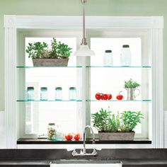 Glass shelves above a kitchen sink add interest and block the view of the neighbors. | Photo: Helen Norman | thisoldhouse.com