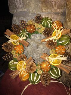 A stunning wreath. Dried green oranges and orange oranges, pine cones and bunches of cinnamon fill this wreath. Smells divine. Base is green moss wreath.
