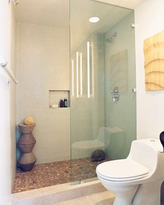 """Flat, smooth stones give the shower the look of a clear streambed. To construct the shower stand, five concrete """"bowls"""" were cast and stacked one on top of the other; it makes a convenient spot for soap and sponges. A cubby holds shampoo bottles and other necessities without interrupting the wall's clean line."""