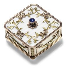 A Fabergé two-colour gold and enamel bell push, workmaster Victor Aarne, St Petersburg, circa 1895. In neoclassical taste, square with canted corners, the surface enamelled in translucent pearl white over wavy engine-turning within bright-cut border mounts, the top applied with conjoined ribbon-tied green gold palm sprays centring the cabochon sapphire push piece, the sides with laurel festoons, bun feet.
