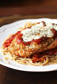 Oven-Baked Chicken Parmesan - A lighter chicken parmesan recipe that's baked, not fried. This classic Oven Baked Chicken Parmesan is a lighter version of an Italian classic: it's baked, not fried and served over whole wheat pasta. I Love Food, Good Food, Yummy Food, Oven Baked Chicken Parmesan, Oven Chicken, Grilled Chicken, Chicken Parmesian, Chicken Tenders, Baked Chicken Parmigiana Recipe