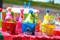 "I bought plastic 90¢ buckets from the party store to hold the kids' favors.  I just stuck paper characters on the bucket to match the color.  The favors were ""take & toss"" Sesame Street sippy cups, silly bands, a Sesame Street activity book (from the dollar bins at Target) & crayons."