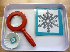 Snowflake matching tray with magnifying glass, for winter preschool science and discovery.