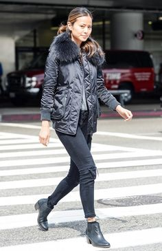 Jamie Chung wears black cuffed skinny jeans, a black parka, and black heeled booties.