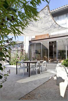 Terrasse reposante avec sa tendue, réaménagée par le réseau d'architectes Archionline dans une maison en pierre