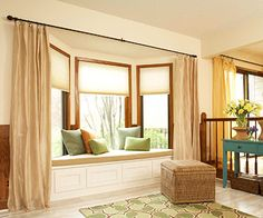 Bay window with roller shades for the windows, as well as long drapes flanking either side