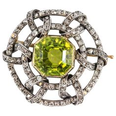 Rare and unusual antique 19th century peridot, diamond and 14K yellow gold brooch by Fabergé. The focal point is a richly colored peridot stone, approx. 19cts total weight, surrounded by high grade round brilliant cut diamonds over a 14K yellow gold setting.