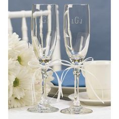 Heart's Desire Toasting Flute Set includes two toasting flutes. Each flute is made of clear glass. They feature a classic flute design and shape with a thick and sturdy base, a thin stem, and a glass bowl on top in a traditional flute shape. The top of each stem is decorated with a white satin ribbon bow. Hanging from each bow is a pair of dangling crystal heart charms.  This item can be personalized.