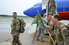 GREENVILLE, N.C. - Army Capt. Leland Pearson, commander of the North Carolina National Guard's 514th Military Police Company, his unit guideon bearer and other Soldiers deplane at Pitt-Greenville Airport before the unit marched in formation to their Readiness Center a short distance away here, May 18. The unit's 120 Soldiers flew into and reunited with friends, families and loved ones after being deployed in Afghanistan for nearly a year.