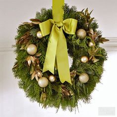There are pretty, elegant ways to give a design boost to a classic evergreen wreath. Here, glittery holiday balls and spray-painted bay leaves supply a golden gloss. Choose a silky ribbon in a complementary color to both the wreath accents and the greenery./