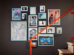 Eine braune Wand mit blauen, weißen und schwarzen Rahmen in unterschiedlichen Größen, in denen Poster und Familienfotos zu sehen sind. An die Wand gebracht u. a. mit MÅTTEBY Aufhängeschablone im 4er-Set.