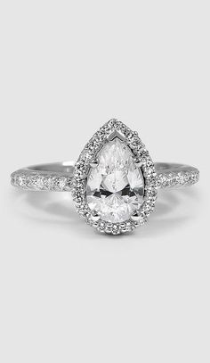 An intricate halo of pavé-set diamonds embraces and accentuates the center oval diamond of this brilliant antique style ring.
