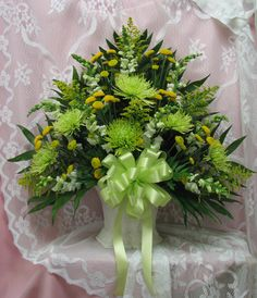 Sympathy Mache in green and yellow featuring mums. Appropriate to be sent by family members or friends