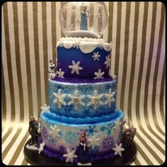 """3 tier Disney Frozen theme cake. 10"""" vanilla cake all airbrushed using stencils in purple faded into blue. 8"""" tier vanilla airbrushed sky blue faded into lighter Skye blue using stencils. 6"""" dummy cake airbrushed purple faded into blue topped with fondant snow. Globe is filled with sanding sugar and the whole cake is adorned with fondant snowflakes! https://www.facebook.com/KassCrafts"""