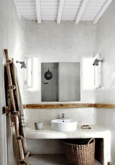 bathroom inspiration: exposed wooden beams, stucco countertop and walls, rustic wooden ladder for towels