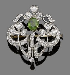 A demantoid garnet brooch/pendant  Of abstract design with shamrock detail, centrally-set with an oval-cut demantoid garnet, within a brilliant-cut diamond surround, diamonds approx. 1.40cts total, width 3.0cm Edwardian with elements or Art Nouveau or inspired by those periods.