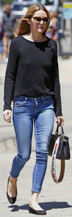 Who made Olivia Palermo's brown cat sunglasses, black sweater, blue skinny jeans, black suede ballet flat shoes, and handbag?