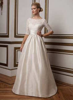 Soft lace Sabrina neckline ball gown is cinched in at the natural waist by a classic Mikado cummerbund. The pearl and bead trimmed neckline and sleeves, pocketed Mikado skirt and V-back give this gown a classic 1960's feeling. https://www.justinalexanderbridal.com/wedding_dresses/8816
