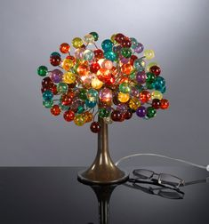A beautiful table lamp with shades made of a bunch of multicolored bubbles in different sizes. The table lamp is handmade from polyester balls