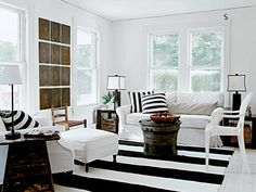 A crisp spin on cottage decorating gives this living room graphic punch. White slipcovers are set off with black accents and warm wood tones. The windows are left bare, since privacy is not an issue, and the clean walls set off the powerful play of stripes. (Photo: Laura Moss)