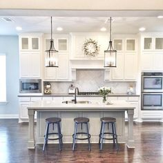 white cabinets and light greige island. Love lights too