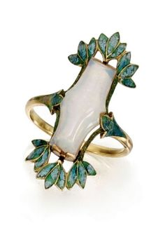 Georges Fouquet | Gold, Opal and Enamel Ring. Circa 1900-1910. Set in the center with a fancy-shaped opal, within a frame of foliate design applied with bluish-green enamel.