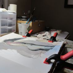 My work table where I work on my sketchbook projects. The clamps keep the paper from buckling as it gets wet with paint layers.