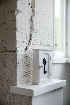 Olohuoneen tapetoidussa seinässä jätettiin esille 1930-luvun tiiliseinää. Avainkaappi on Udesen Danmark.