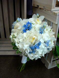 Hydrangea, stock, cymbidium orchids, blue delphinium and variegated pittosporum
