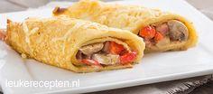 Gevulde pannenkoekrolletjes met paprika, champignons en ham bestrooid met kaas
