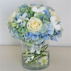 Pale blue-green hydrangea, avalanche roses and white singapore orchids make a gorgeous table centre. This one is low and the inside of the vase is decorated with orchid flowers threaded onto grass for an unusual contemporary touch. The idea can be adapted to make a striking tall version too, have  a look at Lisa's wedding a couple of posts down.