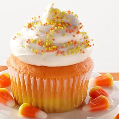 Inspired by Halloween's signature candy, these bright cupcakes feature vibrant layers of orange and yellow cake topped with creamy white frosting and sprinkles.