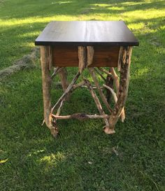This rustic table would look great in any Adirondack styled home . It has a  dark stained top   , with drift wood legs and Stick work .