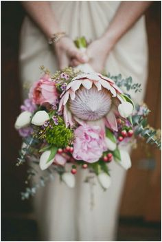 Beautiful & Uniquely Arranged Bridal Bouquet: Pink King Protea, Pink Peonies, Pink Cabbage Roses, Lavender Wax Flower, White Tulips, Green Trick Dianthus, Red Hypericum Berries, & Baby Eucalyptus·····