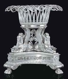 A GEORGE IV SILVER CENTERPIECE MARK OF PAUL STORR, LONDON, 1820 On volute and paw feet, the cruciform base applied with thyrsus and flowerheads, with four sphinxes supporting a reeded basket, with conforming ropework and acanthus decoration, with later silver-plate liner, the base engraved with a later monogram and Continental coronet, the centerpiece possibly reduced in height