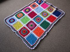 Multi colour granny square baby blanket or pram rug available at www.woollygoods.com