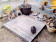 """Teacher Tom's """"Little World"""" created using a wooden platform (made from old fence posts) and incorporating rocks, a basket of wood and pot plants. Endless possibilities!!"""