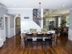 The dining area is now integrated within the open living space and features a large, rustic farm table, black curved-back chairs and wrought-iron chandelier.