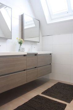 by Holly Marder  The pale oak tones throughout the rest of the house are carried through to the bathroom, where this family of four shares a contemporary double vanity with several deep drawers for storing bathroom products.