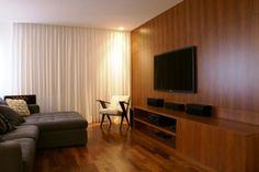O uso da madeira no piso e na parede não foi meramente estético. A ideia da arquiteta Gisele Emery era melhorar a acústica do espaço de 50 m² com esse material. O sofá na cor cinza e o branco da cortina completam a sala desta residência em São Paulo (SP).
