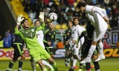 Mexico goalkeeper Jose de Jesus Corona tries to block a header by Bolivia's Danny Bejarano during the Copa America Group A match at the Sausalito Stadium in Vina del Mar, Chile.