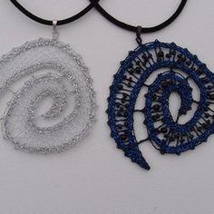 Přívěsky spirálovitého tvaru, více či méně zaoblené - ve stříbře nebo v tmavě modré v kombinaci s korálky. Dalším typem jsou pravidelné kulaté přívěsky, které jsou orámované kovovým kroužkem - ve skutečnosti se jedná o náramky.