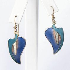 The ever-stylish calla lily, interpreted by Laurel Burch in shades of teal green and purplish-blue. A graceful sweep of teal curves down one side of the drop earring, while on the other side a blue petal cradles the hanging white stamen surround...