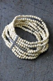 """""""Magdalene"""" This beautiful seven strand stretch bracelet symbolizes the love and mercy of Christ washing us white as snow. Each ivory bone beaded strand with silver-tone accent beads is passed through a silver cross. Christ has you covered."""