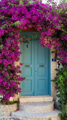Alaçatı, İzmir, Turkey. Purple bougainvillea and turquoise double door.