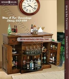 695084 Howard Miller Wine and Bar Furnishings This Hide-A-Bar console has raised door panels and offers generous room for wine and spirits. Each side features an adjustable shelf and storage on the inside of each door.The center of the cabinet features a lazy susan style pivoting door with two fixed shelves providing additional room for bottle and glass storage. The top is a planked style look with a hand planed surface and various forms of distressing.